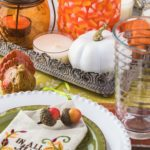 Close up of tableset with colorful plates, silverware and center piece arrangement for Thanksgiving party.