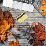 Workspace with laptop, maple yellow and red leaves, credit card on grey wooden background. Flat lay, top view.